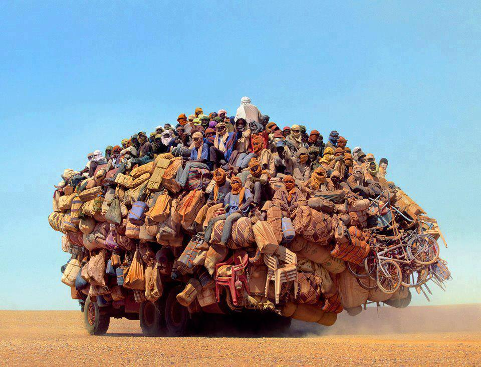 many people crowd atop a truck in the desert